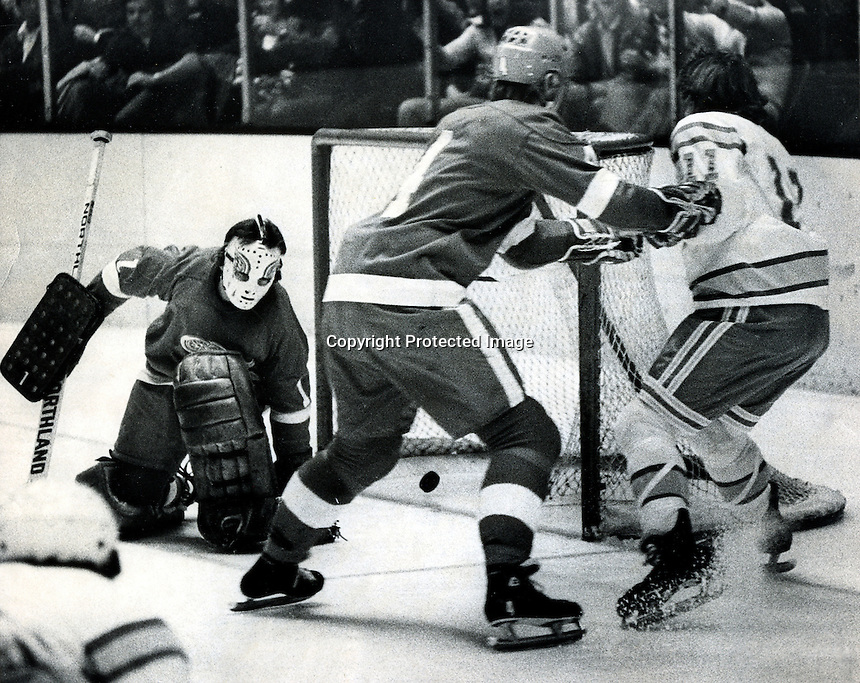 Seals action,vs. Detroit Red Wings.. #11 Ron Huston and Wings Thommie Bergman in front of goalie Jim Rutherford. (1975 photo by Ron Riesterer)