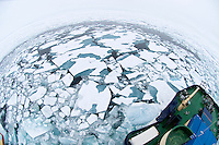 Fisheye view of a scientific research ship breaking through ice floes in the Arctic Ocean.