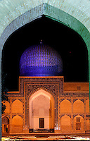 Low angle view of the Gur-Emir Mausoleum, 1417-20,  framed by the monumental entrance arch, Samarkand, Uzbekistan, pictured on July 14, 2010, floodlit at night. Gur-Emir Mausoleum, or Tomb of the Ruler, was built by Timur in 1404 for his favourite grandson, Mohammed Sultan, and became the mausoleum for the Timurid dynasty. The simply formed building is an octagonal drum beneath an azure fluted dome (diameter: 15m, height: 12.5m). Its walls are tiled in blue and white geometric and epigraphic patterns including the words 'God is Immortal' in 3m. high white Kufic script around the top of the drum. Samarkand, a city on the Silk Road, founded as Afrosiab in the 7th century BC, is a meeting point for the world's cultures. Its most important development was in the Timurid period, 14th to 15th centuries. Picture by Manuel Cohen.