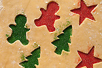 Dough with cookies cut outs sprinkled with with red and green sprinkles