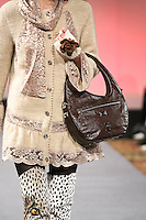 Model walks runway in an outfit from the Janerations Fall 2012 collection, by Janina Stankiene, and a handbag from Uvo Luxury by Gigi Karmous-Edwards, during Couture Fashion Week New York Fall 2012.