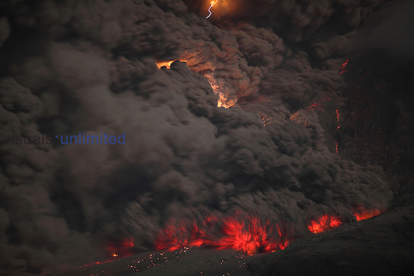 Massive glowing pyroclastic flows with volcanic lightning descend flank of Sinabung Volcano at night, Sumatra, Indonesia.