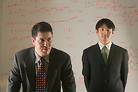 Portrait of two Economic Research associates at the Federal Reserve Bank - Kansas City.  They are in front of a white board with economic formulas written on them.