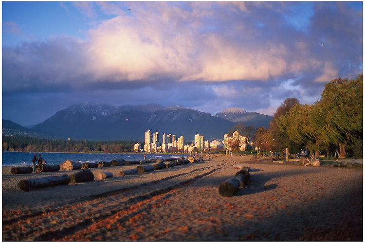 Wind whipping across Kitsilano Beach, with towers of the West End of Vancouver bathed in sunlight, and the mountains of North Vancouver.