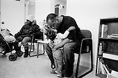 Cleveland, Ohio.March 25, 2008 ..After being evicted out of their apartment without notice, because the landlord foreclosed on the property they were renting, even though they had paid the rent, Darin Roseberry, 46 yrs old, and his two daughters, Ayuaunie, 17 months, and Denise 20 yrs, spent the night on a bus to keep warm. All of their belongings ended up on the street, and they ended up at Catholic Charities Emergency Center in Cleveland. Catholic Charities fed them and offered them a night in a hotel before they were spilt up and place in separate shelters, which tend to be over crowded and violent...Darin gives his youngest daughter a hug after being on the streets for 24 hours.
