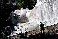 Man in silhouette against Tuong Phat Nam (white reclining Buddha), on Ta Cu mountain, Binh Thuan Province, Vietnam. At 49 metres long, the Buddha is the longest in Vietnam and one of the longest reclining Buddhas in Asia.