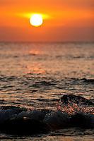 The sun sets as waves splash over rocks as seen from Hideaways beach in Princeville, Kauai.