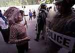 A woman talks with police officers as displaced residents of Boeung Lake in Phnom Penh, who were left homeless after the government allowed a private developer to move them out and fill in the lake, attempt to protest in the Cambodian capital on December 10, 2012. They planned to take their protest to the prime minister's office, but police stopped them far short of their goal. Their protest took place on International Human Rights Day.