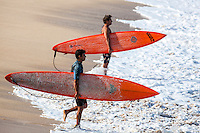 Two Caucasian male surfers holding orange surfboards gauge where they plan to paddle out to for big waves, Waimea Bay, North Shore, O'ahu.