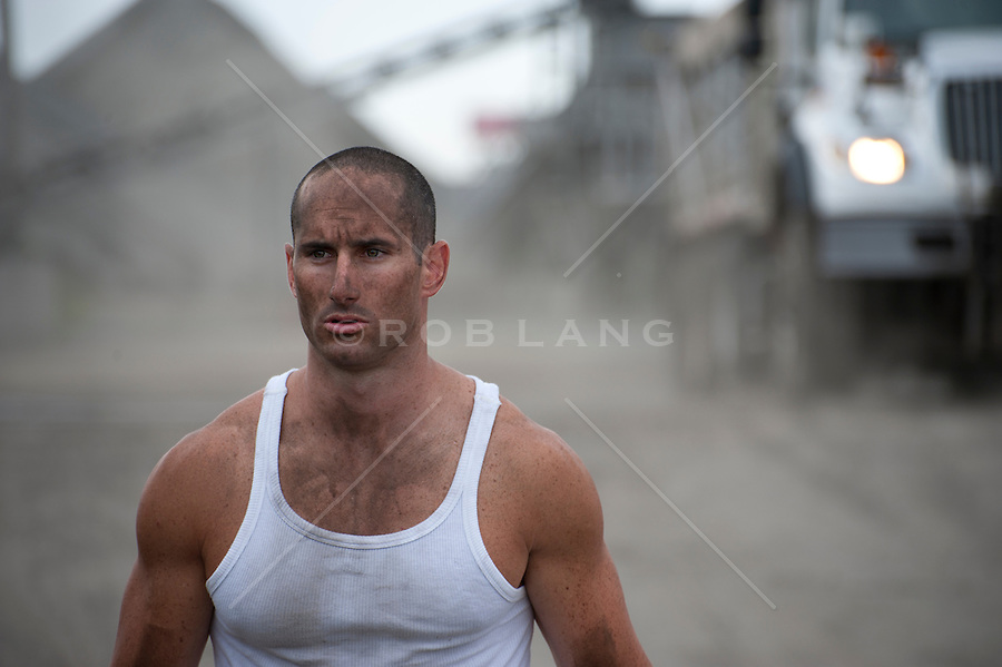 man in a tank top covered in dirt at a construction site