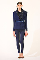 Model wears a draped lapel jacket, feather embellished sweater, illusion pocket skinny trousers, and illusion belt by Fiona Cibani, for the Ports 1961 Pre-Fall 2011 L'heure bleue collection, December 8, 2010.
