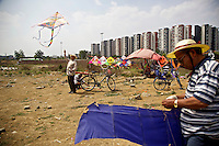 Hobbyists take advantage of government land clearance to fly kites in the congested southwestern Chinese megapolis of Chengdu. Here, a plot of farmland was recently cleared and flattened to make way for urban development. Hobbyists would enjoy the land until construction starts, and look for new pastures. The Chinese government plans to move 250 million rural residents into urban areas over the coming dozen years though it is unclear whether people want to move and where the money for this project will come from. Further urbanisation is meant to drive up consumption to counterbalance an export orientated economy and end subsistence farming but the drive to get people off the land is causing tens of thousands of protests each year. /Felix Features