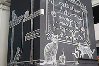 The menu board at the Cat Cafe on the Bowery in New York on its grand opening day, Thursday, April 24, 2014. Purina has teamed with the North Shore Animal League to open the pop-up cafe where cat aficionados are not afraid to get a little fur on their clothing while they snuggle the adoptable cats, drink cappuccino and eat pastries. The kitties are free-range around the store and the customers can pet them, pick them up and play with them. Cat cafes are already big in Japan and this pop-up store is a first for New York. The event only goes until April 27 when you can take your adopted kittie home. (© Frances M. Roberts)