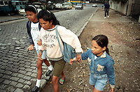 Somália da Silva walks two of her four school-age daughters, Lizandra, left, and Milani, to an underfunded public school each morning. Two of the girls attended classes in the morning and another two in the afternoon, requiring her to make four trips each day through the unsafe streets of the slum.