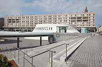 Le Volcan or the Volcano, auditorium opened 1982, designed by Oscar Niemeyer, 1907-2012, and Jean-Maur Lyonnet, at the Maison de la Culture du Havre, Le Havre, Normandy, France. Behind are apartment buildings designed by Auguste Perret, 1874-1954, who led the reconstruction of Le Havre in the 1950s, after the town was completely destroyed in WWII. The large volcano contains a 1200 seat theatre and 350 seat cinema, while the small volcano (seen here) has a 500 seat hall and 80 seat auditorium and is now used as a reference library. The forum is built from concrete and the buildings are linked and accessed via ramps. The centre of Le Havre is listed as a UNESCO World Heritage Site. Picture by Manuel Cohen