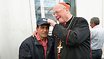 Cardinal Timothy Dolan, the archbishop of New York and chair of the Catholic Near East Welfare Association, jokes with a man wearing a Yankees baseball hat in the waiting area of a clinic for internally displaced people in Ankawa, near Erbil, Iraq. The clinic is run by the Dominican Sisters of St. Catherine of Siena, who were themselves displaced by ISIS in 2014. The Yankees are a baseball team.