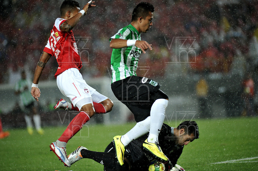 BOGOTA - COLOMBIA -07 -05-2014: Francisco Meza (Izq.) y Camilo Vargas (Cent.) jugadores de Independiente Santa Fe disputan el balón con Fernando Uribe (Der.) jugador de Atletico Nacional, durante partido de ida entre Independiente Santa Fe y Atletico Nacional, por las semifinales de la Liga Postobon I-2014, jugado en el estadio Nemesio Camacho El Campin de la ciudad de Bogota./ Francisco Meza (L) and Camilo Vargas (C) players of Independiente Santa Fe struggle for the ball with Fernando Uribe (R) player of Atletico Nacional, during a match for the first leg between Independiente Santa Fe and Atletico Nacional, for the semifinals of the Liga Postobon I -2014 at the Nemesio Camacho El Campin Stadium in Bogota city, Photos: VizzorImage  / Luis Ramirez / Staff.