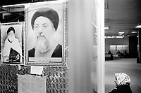 Iraq. Baghdad. Medical City hospital. A woman, wearing the hidjab (islamic headscarf) to cover her hair, sits near the pictures of the ayatollah Mohammed Al Sadr (killed by the Saddam Husssein regime) and the ayatollah Mohammed Baqer el-Hakim (killed in a car bomb attack in Najaf on august 29 2003 ). The word hijab (or hidjab) refers to both the veil covering the head and traditionally worn by muslim women (Islamic headscarf), but also the  modest muslim styles of dress in general. 20.02.04 © 2004 Didier Ruef