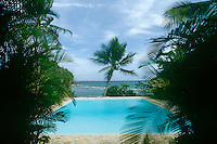 The turquoise waters of the palm-fringed outdoor swimming pool, which has views over the beach