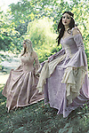 Two pretty young women in renaissance costumes outdoors looking fancy and regal
