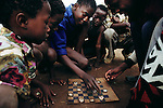 A group of children on the street play checkers with beer bottle caps on a homemade checkerboard in Soweto, South Africa. Soweto is the nickname of Southwest Township, a sprawling lawless community outside Johannesburg. Published in Material World on page 26. South Africa. Material World Project.