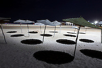 ESSAOUIRA, MOROCCO - MAY 8 : a low angle view of beach umbrellas at night on May 8, 2009 in Essaouira, Morocco. Black circles of shadow are thrown onto white sand by the bright lighting. Essaouira, on the windswept Atlantic coast of Morocco, was re-built in the 18th century by French architect Theodore Cornut to the orders of Sultan Ben Abdullah. Surrounded by ramparts it is a charming small town now becoming more popular with tourists. (Photo by Manuel Cohen)