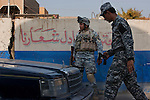Iraqi federal policemen search cars at a checkpoint in southwest Baghdad August 24, 2010.  .