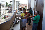 Students practice violin on the balcony of Ecole de Musique Dessaix Baptiste in Jacmel, Haiti