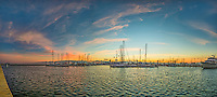 This is panorama of the marina in Corpus Christi at sunrise with the colorful sky in the background and the sea wall running along for a good distance.