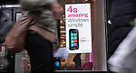 People walk next to a banner of the new Nokia Windows Smartphone Lumia 710 in a T-Mobile store in New York, United States. 11/01/12.  Photo by Kena Betancur / VIEWpress.