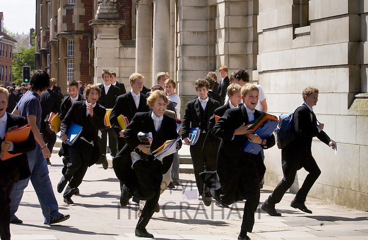 Eton College schoolboys in traditional white tie and tails running after the end of lessons, Eton, UK