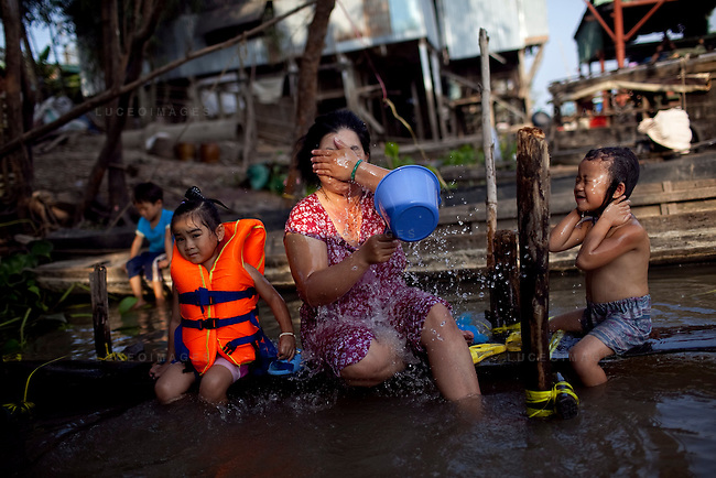"Kim Yen, 36, bathes with her two daughters, Yen, 4, left, and Thuy, 5, on the Hau Giang River, a tributary of the Mekong River, in Chau Doc, in the An Giang Province, Vietnam. When the Mekong River reaches Vietnam it splits into two smaller riveres. The ""Tien Giang"", which means ""upper river"" and the ""Hau Giang"", which means ""lower river"". Photo taken on Monday, December 7, 2009. Kevin German / Luceo Images"