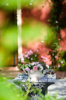 A garden table with tea served in delicate china cups and a bowl of freshly cut roses viewed through the garden foliage