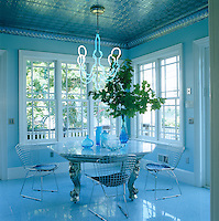 The breakfast room is furnished with an eclectic combination of designer chairs and a table found in a flea market illuminated by an Edison chandelier designed by Matt Dilling