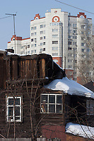 Barnaul, Altai Region, Siberia, Russia, 24/02/2011..New apartment buildings behind still occupied wooden homes in Barnaul city centre.