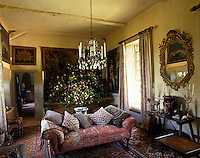 Tapestries and antique paintings cover the walls of this drawing room and a large crystal chandelier hangs over a sofa filled with cushions