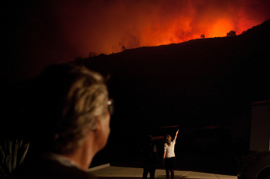 "Santa Barbara, Calif., May 6, 2009 - Charlie Duff, left, watches the Jesusita Fire as his wife Cathy Duff points out to their neighbor Aaron Douglas, where there second home is located just over the ridge. The couple owns two homes in the area. There primary home (seen here) was nearly destroyed by last year's Tea Fire, but that blaze also knocked back the grass and brush that would be fuel for this fire. The blaze was quickly approaching their second home. Charlie added, ""It will probably be gone in a few more minutes."" The blaze destroyed several homes in the area as well as knocking out the 220-kilovolt Goleta transmission line which are the primary source for Santa Barbara County.  Governor Arnold Schwarzenegger has declared a state of emergency. During a 10 am press conference the Governor added that 5,400 homes (13,575 people) have been evacuated, 3,500 homes are considered threatened and several dozen have been lost, though no official number has been released."