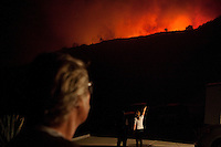 """Santa Barbara, Calif., May 6, 2009 - Charlie Duff, left, watches the Jesusita Fire as his wife Cathy Duff points out to their neighbor Aaron Douglas, where there second home is located just over the ridge. The couple owns two homes in the area. There primary home (seen here) was nearly destroyed by last year's Tea Fire, but that blaze also knocked back the grass and brush that would be fuel for this fire. The blaze was quickly approaching their second home. Charlie added, """"It will probably be gone in a few more minutes."""" The blaze destroyed several homes in the area as well as knocking out the 220-kilovolt Goleta transmission line which are the primary source for Santa Barbara County.  Governor Arnold Schwarzenegger has declared a state of emergency. During a 10 am press conference the Governor added that 5,400 homes (13,575 people) have been evacuated, 3,500 homes are considered threatened and several dozen have been lost, though no official number has been released."""