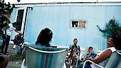 Garden City, Kansas, USA, August 2011:.Mexican immigrants by their trailer home. Many hispanic immigrants from Mexico and Salvador live in the trailers. Most of them came here to work at Tyson meatpacking plant, which kills and processes 6 thousand cattle a day. Kansas dominates American beef industry, by producing one quarter of all beef in the USA, while being heavily dependent on cheap immigrant labour..(Photo by Piotr Malecki / Napo Images)..Garden City, Kansas, Stany Zjednoczone, Sierpien 2011:.Osiedle przyczep-domow. Duzo emigrantow z Meksyku i Salwadoru mieszka w przyczepach samochodowych, a pracuje w zakladach miesnych Tyson, ktore zabijaja i przerabiaja 6 tysiecy sztuk bydla dziennie. Stan Kansas zdominowal rynek wolowiny w Stanach Zjednoczonych, produkujac jedna czwarta calej amerykanskiej wolowiny. Amerykanski przemysl miesny jest bardzo uzalezniony od taniej sily roboczej, ktora daja emigranci..Fot: Piotr Malecki / Napo Images.