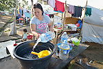 Rosita Unidas, whose family was displaced by Typhoon Haiyan in November 2013, washes dishes in front of her tent in a temporary shelter at the West Campus of the Northern Iloilo Polytchnic State College in Estancia, Philippines. The storm was known locally as Yolanda. Residents of this camp have been assisted by the ACT Alliance. More than 100 families remained in the camp in February 2014, many of them refusing to return to a coastline soaked by an oil spill during the typhoon, and uninterested in a government offer to relocate them at a remote location well out of the city.