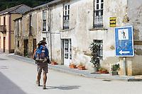 Walker checks sign on Camino de Santiago Pilgrim's Walk, to Santiago de Compostela at Triacastela in Galicia, Spain