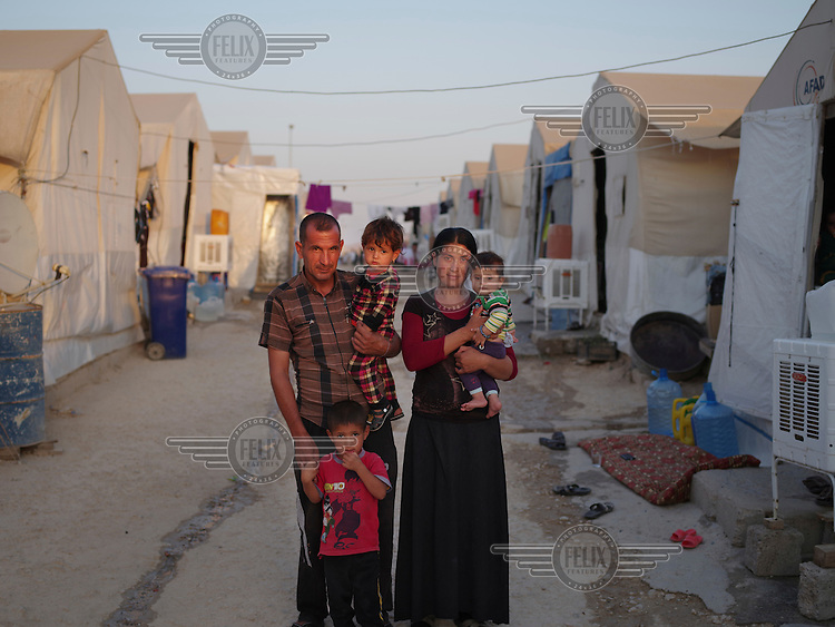 A Yazidi family living in Sharia camp. Haydar, 40, the father said: 'I was working as a cleaner at clinic in Sinjar. I got married to my wife Kamal in November 2013. When ISIS attacked my village Zorav, in the northern part of Sinjar in August 2014, we ran away to Sinjar mountain. My wife gave a birth on the mountain on 6 August. Then we came to this refugee camp. Our home is made of mud and it was totally destroyed by ISIS. I don't want to go back to Sinjar even if Sinjar becomes peaceful in the future. I would like to go to Germany with my family. But we have no money to pay for smugglers.'
