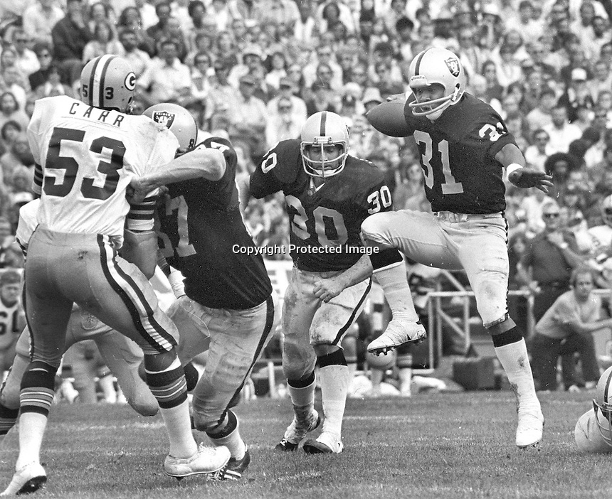 Oakland Raiders Carl Garrett #31 gets blocks from  Dave Casper and Mark Van Eeghen against the Green Bay Packers Carr......(1976 photo by Ron Riesterer)