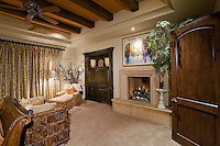 Luxurious master bedroom with beautiful draperies, fireplace and furnishings