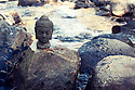 Buddha head on a river boulder.