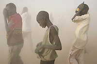 People try to shelter from the dust thrown up by the departing UN WFP (World Food Program) flight at the Twic Olympics in Wunrok, Southern Sudan.