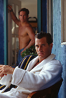 Man in  a bathrobe and shirtless man at home both looking at camera