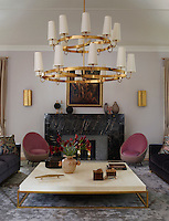 A luxurious living room is furnished with a mix of antiques and contemporary Italian designs. The custom-made armchairs are upholstered in a Lelievre velvet, the custom-made chandelier and 1950s sconces are of brass, and the Venetian painting dates from 1795. The stately fireplace is clad mostly in Noir Saint Laurent, a French marble.