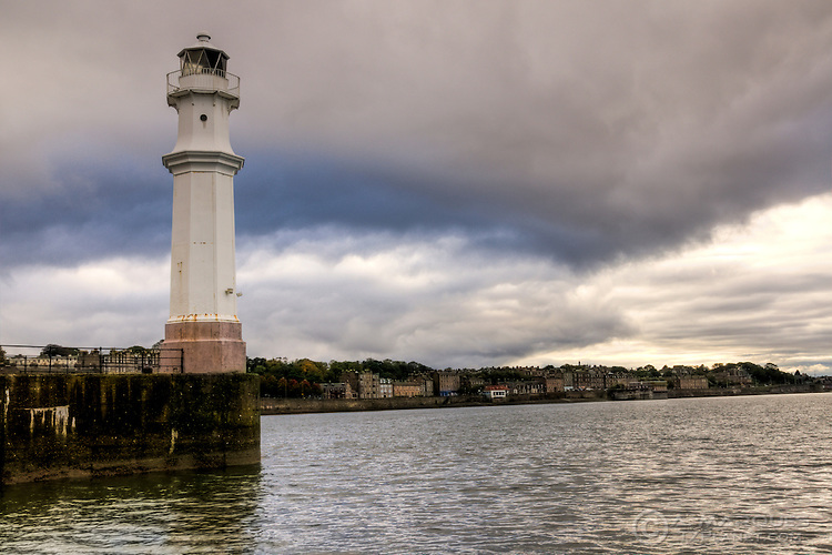Lighthouse at the Newhaven Harbour, Edinburgh, Scotland.  .Newhaven is a district of the city of Edinburgh, at the north of the city, between Leith and Granton. The lighthouse and pier are a favorite spot with local fishermen.