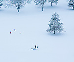 Kids pulling their sleds across the snow after a day of sledding.